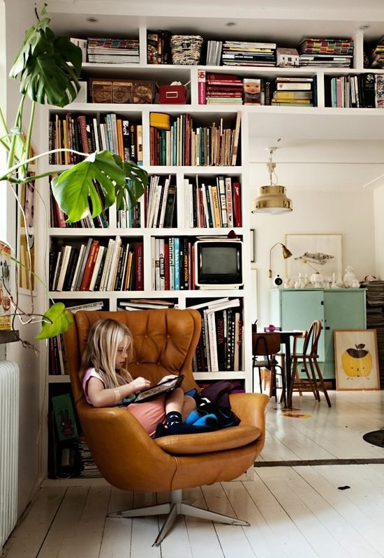 Child reading on chair, surrounded by bookshelves