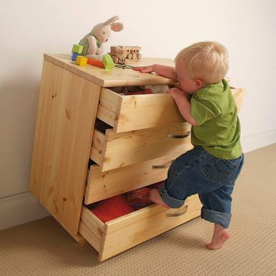 A child attempting to climb a drawer chest