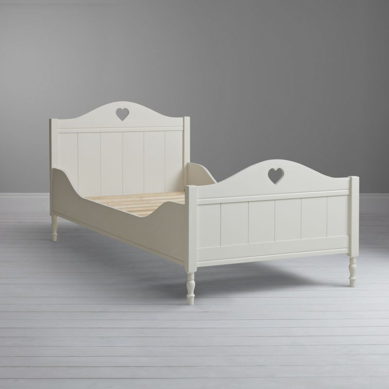 Ivory painted kid's bed with curved styling and heat shaped cut outs