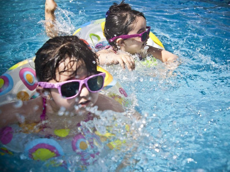Kids in the pool wearing sunglasses