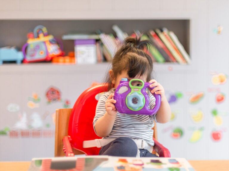 Toddler sat in a highchair and playing with a camera