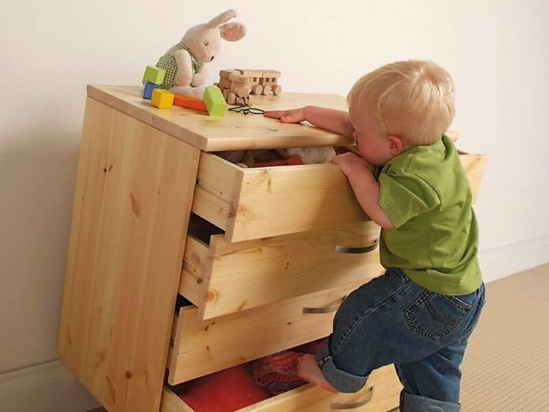 Child attempting to climb a set of drawers