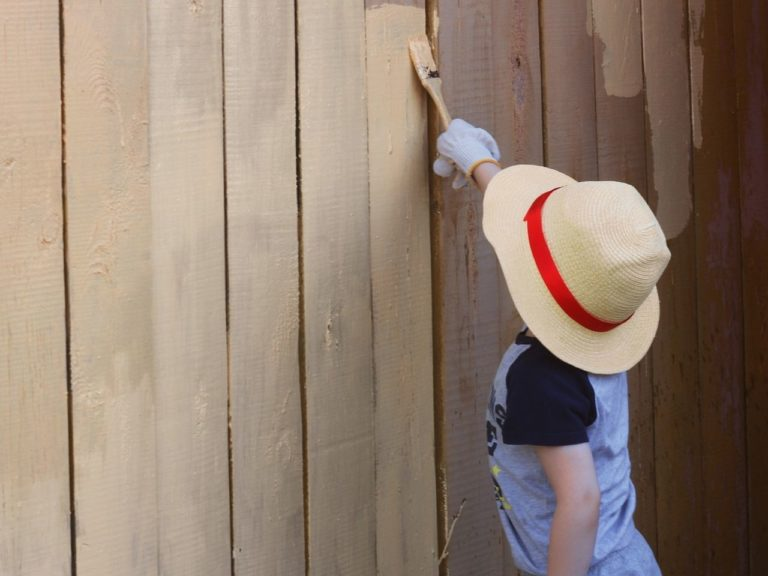 Child painting a fence