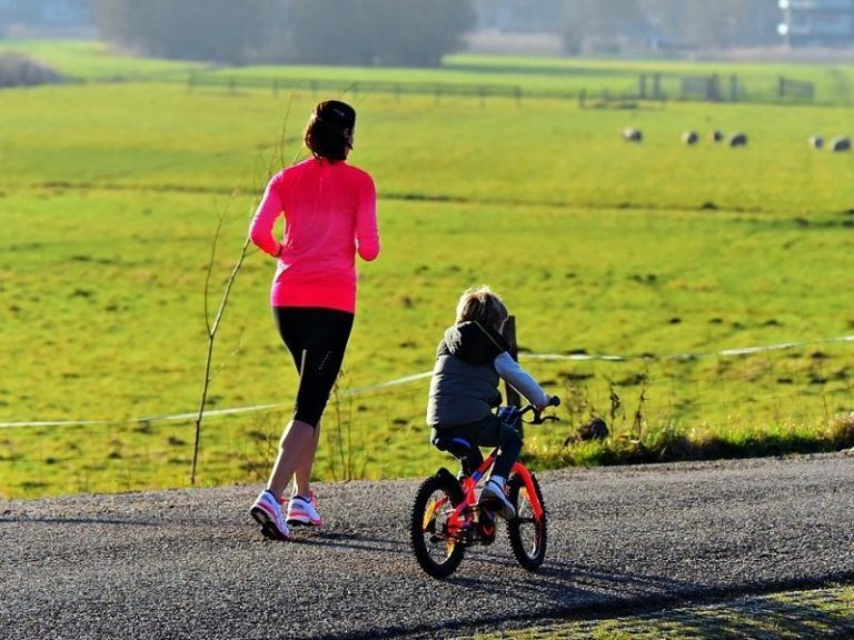Mum jogging with child riding bike