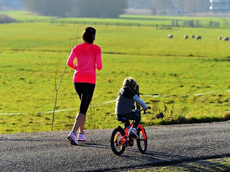 Mum jogging with child riding bike