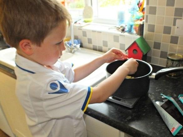 Breaking the chocolate chunks into a saucepan