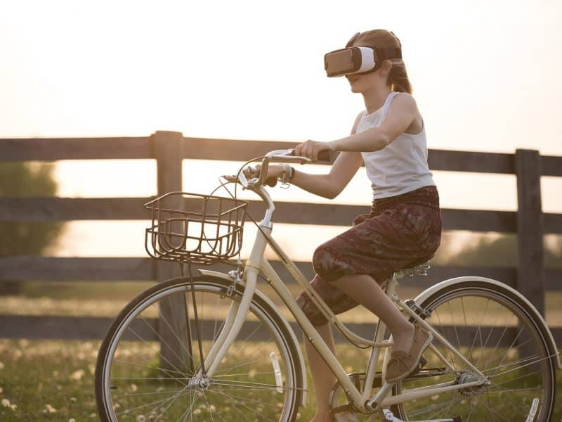 Girl riding bike whilst wearing a VR headset
