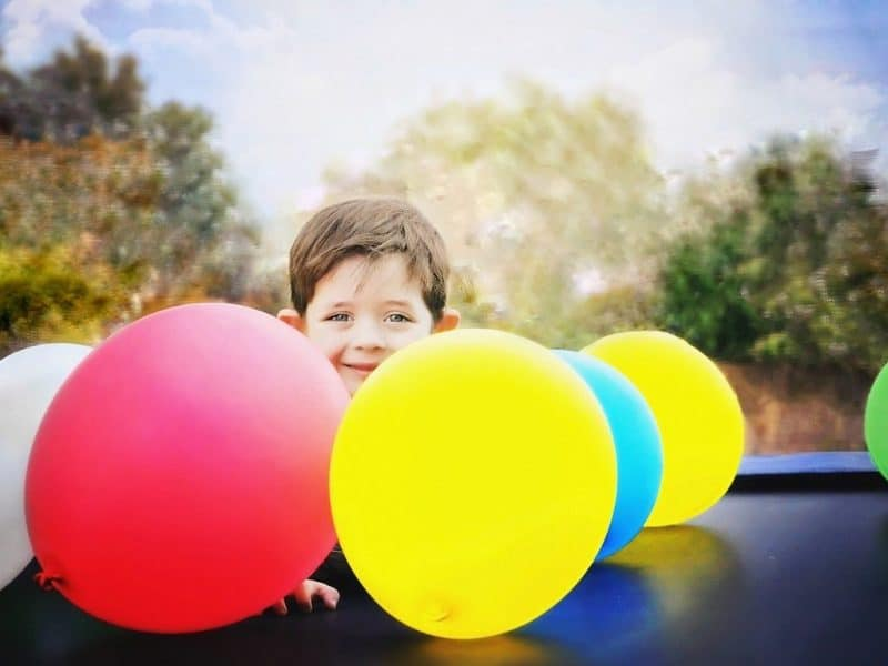Boy with brightly coloured balloons