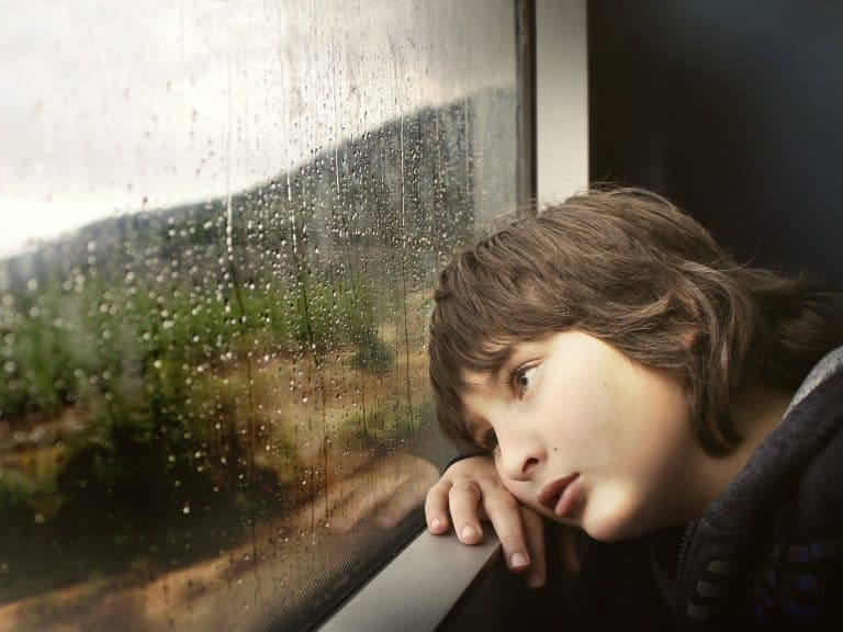 Bored child looking out of a train window in the rain