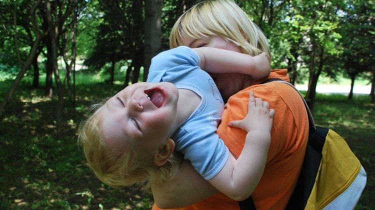 Mum cuddling her playful son