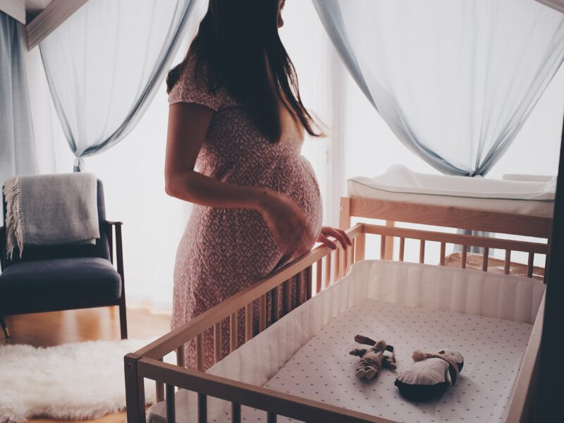 Pregnant mum stood by cot